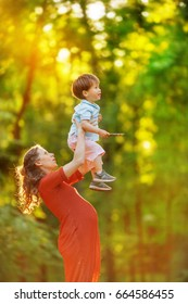 A pregnant woman in a red knitted dress high raises her son, standing on the edge of the forest