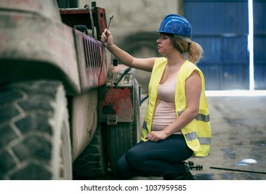 Pregnant woman repairing forklift in concrete factory