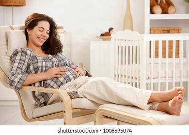 Pregnant woman resting in armchair at home looking down smiling.