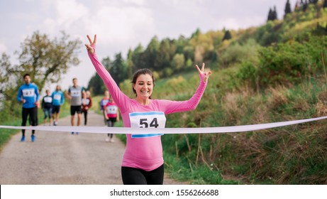 Pregnant woman runner crossing finish line in a race competition in nature.