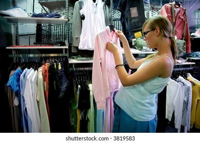 pregnant woman in shop looking at pink jacket