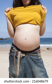 pregnant woman showing her navel at Asturian beach