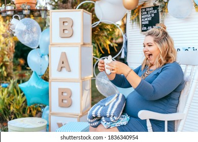 Pregnant woman sits on a Baby shower party setup and looking at the gifts, happy smiling, and exciting