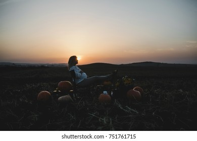 Pregnant woman sits on the chair among pumpkins on the field