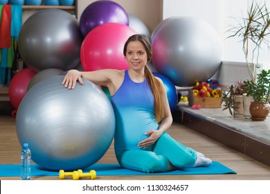 Pregnant woman sits on the mat in the gym, soft focus background