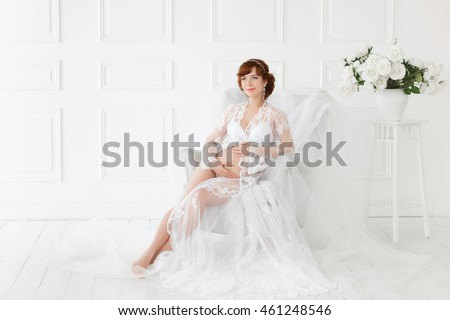 78b860c4b Pregnant woman sitting in a chair in a beautiful white dress boudoir ( negligee).