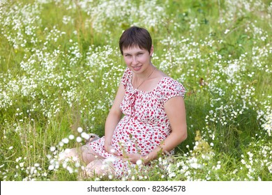 Pregnant woman sitting in chamomile background