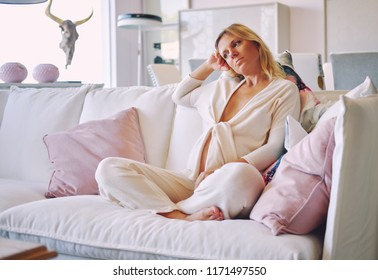 Pregnant woman sitting in couch at lounge room. Young blond pensive, serious bored female in morning dress sitting in modern cozy comfortable sitting room alone
