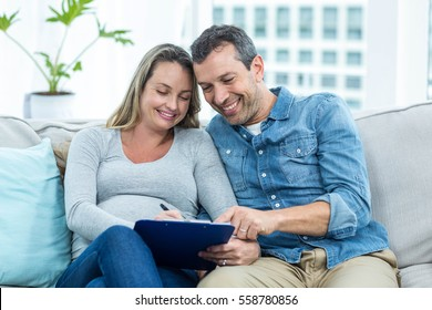 Pregnant woman sitting with man on sofa and writing on clipboard