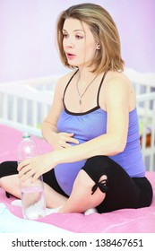 Pregnant woman sitting on bed with water