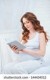 Pregnant woman sitting on bed and reading book