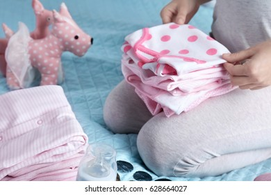 Pregnant woman sitting on bed with pile of baby cloth