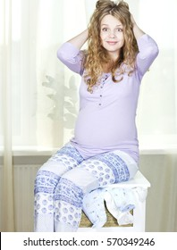 Pregnant woman sitting on the chest of drawers with baby clothes. Pregnant blonde in confusion.