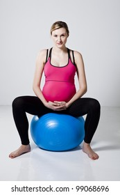 Pregnant woman sitting on a fitness ball and relaxing