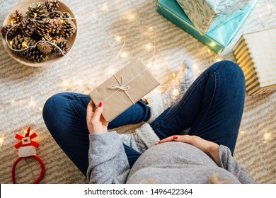 Pregnant woman sitting on floor surrounded with Christmas decorations and hold gift box