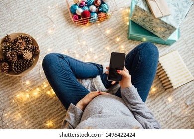 Pregnant woman sitting on floor surrounded with Christmas decorations and gifts and use mobile phone