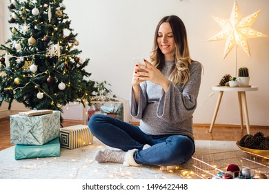 Pregnant woman sitting on floor next to the Christmas tree and use mobile phone