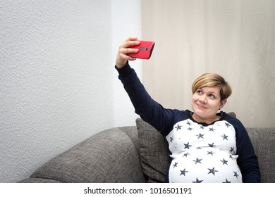 Pregnant Woman sitting on a sofa and making a selfie