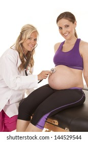 A pregnant woman with a smile on her face having her doctor listen to her belly with a stethoscope