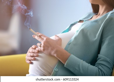 Pregnant woman smoking cigarette at home