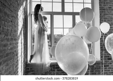 pregnant woman standing in front of window with balloons