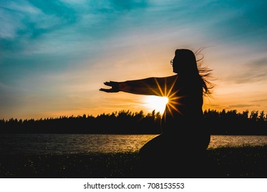Pregnant woman standing at sunset.Pregnant woman doing yoga at sunset.
