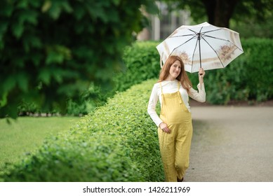 Pregnant woman stands in the rain with an umbrella in park.