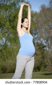 Pregnant woman stretching outdoors