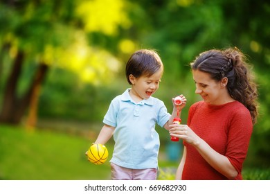 A pregnant woman is teaching her son to inflate soap bubbles for a walk in the park. The boy laughs, holding a small ball in his hands.