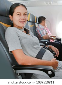 Pregnant woman is traveling by plane sitting at seat with fasten seat belt.