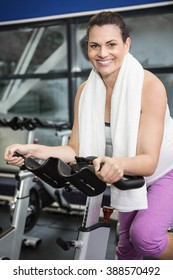 Pregnant woman using exercise bike at the gym