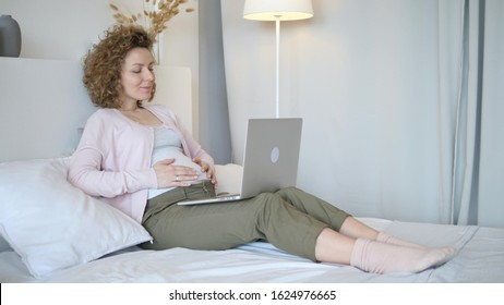 Pregnant Woman Using Laptop Lying On Bed At Home
