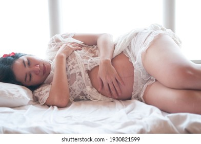 The pregnant woman wearing white clothes. Pregnant woman laying down.