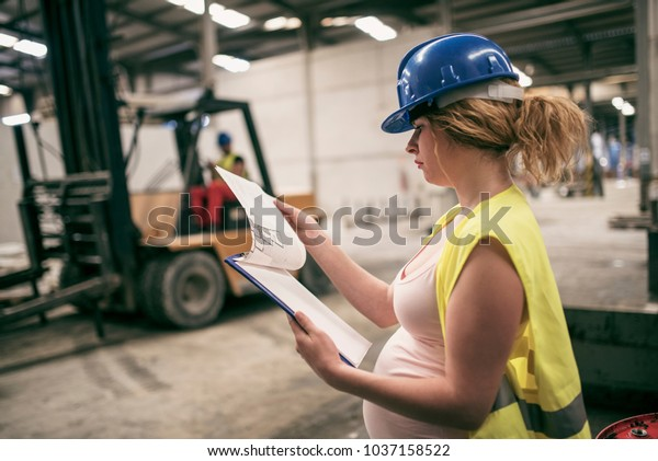 Pregnant woman working in construction factory. Man driving forklift in background
