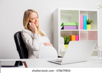 Pregnant woman working in the office and talking on mobile phone