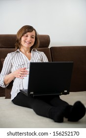 Pregnant woman working on laptop from home on sofa