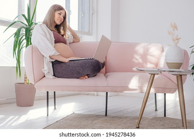 Pregnant woman working via laptop at home. Future mother. Home office. Working mother