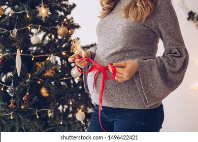 Pregnant woman with wrapped ribbon around her stomach, standing in front of Christmas tree