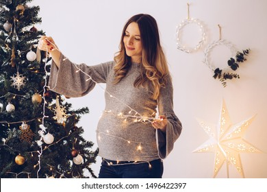 Pregnant woman with wrapped string lights around her stomach, decorating Christmas tree