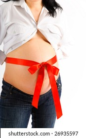 pregnant woman`s belly with a red ribbon bow on white