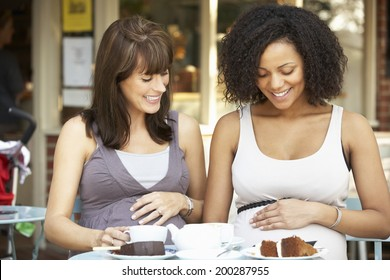 Pregnant women sitting outside cafe