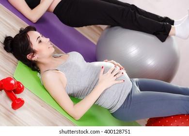 Pregnant Yoga. Prenatal exercise. Beautiful pregnant woman performing yoga. Serenity and joy at prenatal yoga exercises in class. health care. parenting. maternity.