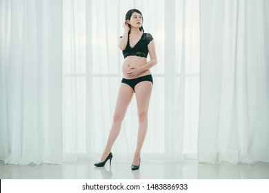 Pregnant young asian chinese girl posing in black lace lingerie and underwear. copy space. full length of future mother in sexy wear and high heeled shoes touching belly with white background.