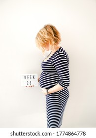 Pregnant young caucasian female touching her growing belly and holding a sign with 28 weeks