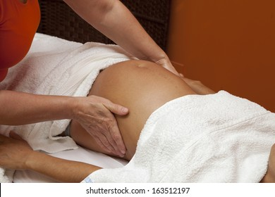Pregnant young latina woman with beautiful skin, being wrapped with a towel, lying on a bed and having a relaxing prenatal massage, various techniques