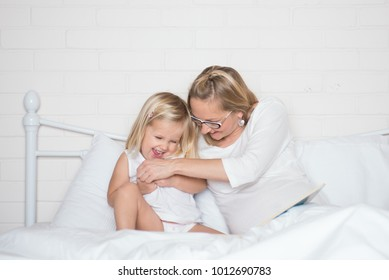 Pregnant young mother and her daughter having fun in the bed