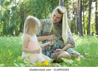 Pregnant young mother with her little daughter spending time in a summer park