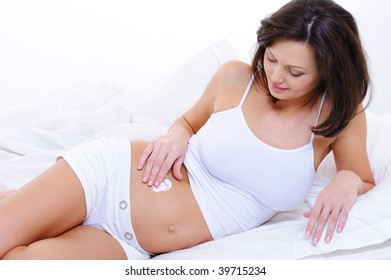 Pregnant young woman applying moisturizer cream on her belly