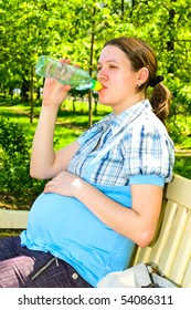 pregnant young woman drinking water