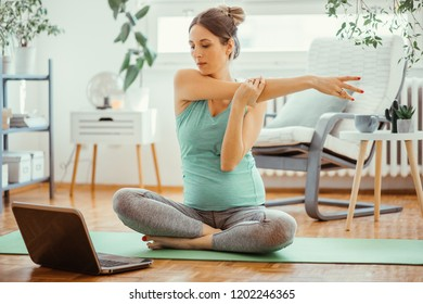Pregnant young woman exercise yoga, and using laptop to find the best exercise program